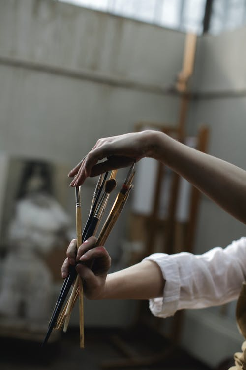 Person in White Long-Sleeve Shirt Holding Paint Brushes