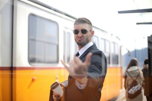 Un Hombre En Traje Negro De Pie Cerca De Blanco Ad Tren Amarillo