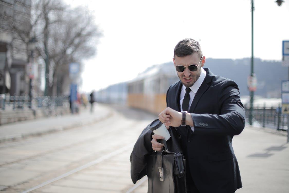 Man in Black Suit Jacket Holding Black Leather Bag