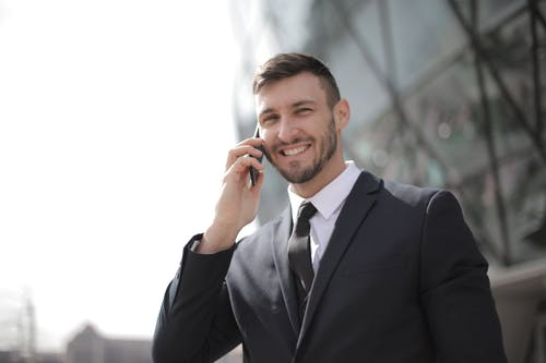 Man in Black Suit Jacket Holding Smartphone