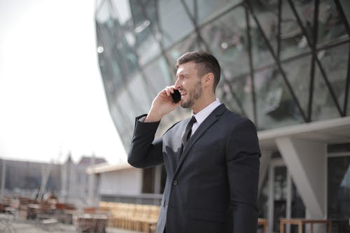 Man in Black Suit Jacket While Using Smartphone