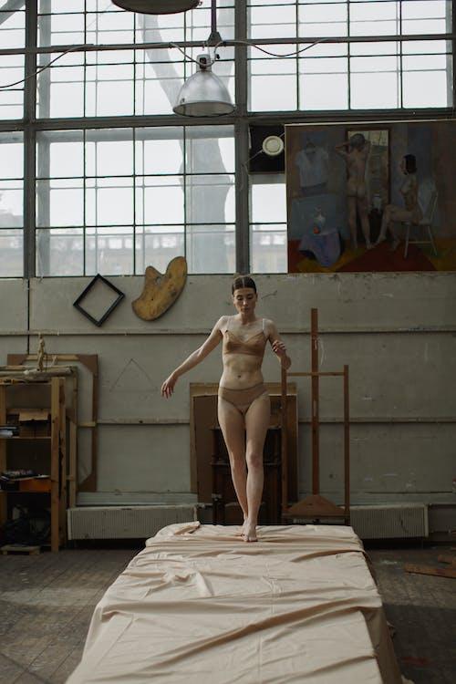 Woman in Beige Bikini Standing on White Bed