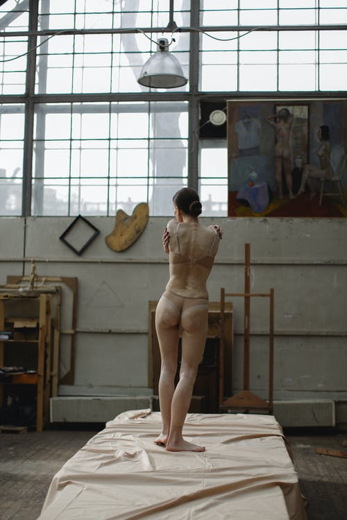 Back View Of A Woman Standing On A Platform Near Window