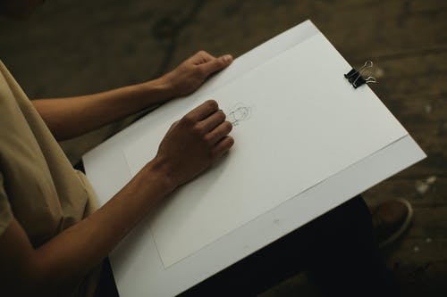 Person Holding White Illustration Board