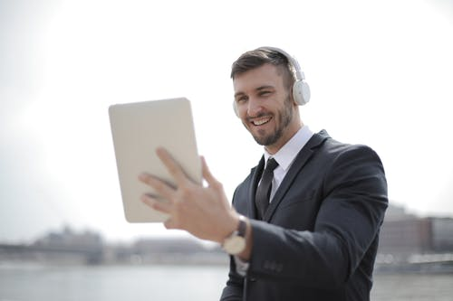Man in Black Suit Jacket Holding a Tablet While Listening to Music