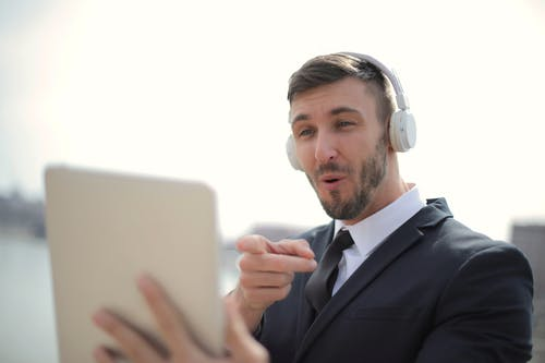 Hombre En Traje Negro Chaqueta Mientras Usa Auriculares Blancos