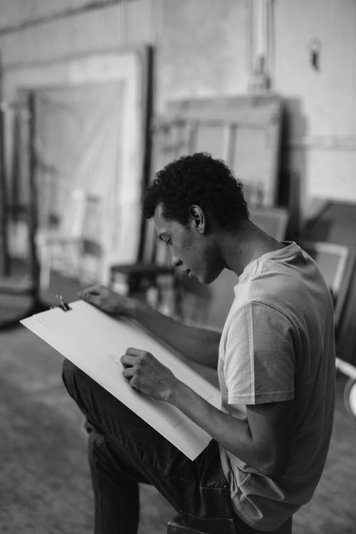 Grayscale Photo Of A Man Sketching On White Cardboard