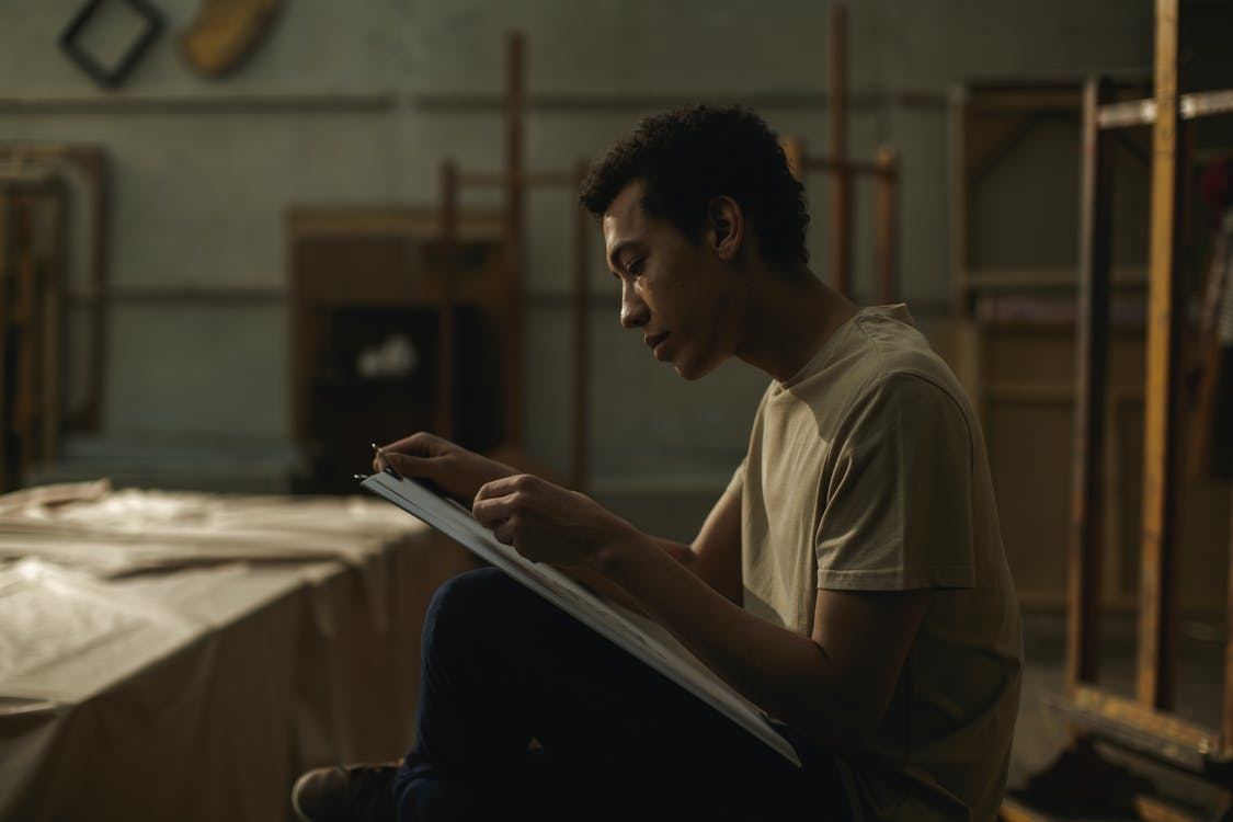 A Man Sketching On A White Cardboard