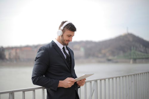 Man in Black Suit Jacket and Black Pants Holding an Tablet While Standing Beside Railings