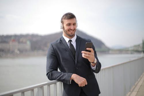 Man in Black Suit Jacket Holding Black Smartphone
