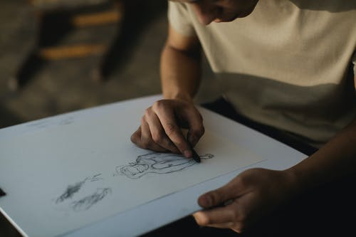 Pessoa Com Camisa Marrom Escrevendo Em Papel Branco