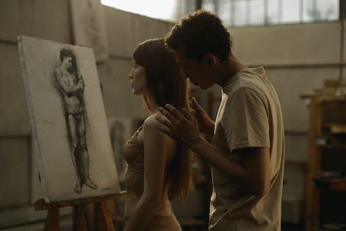 Man in White T-shirt Kissing Woman in White Tank Top