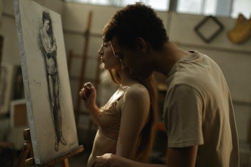 Man in Brown Shirt Kissing Woman in White Tank Top