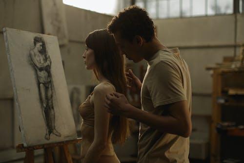 Man in Gray T-shirt Kissing Woman in White Sleeveless Dress