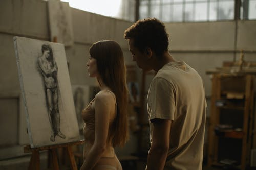Man And Woman Checking The Painting