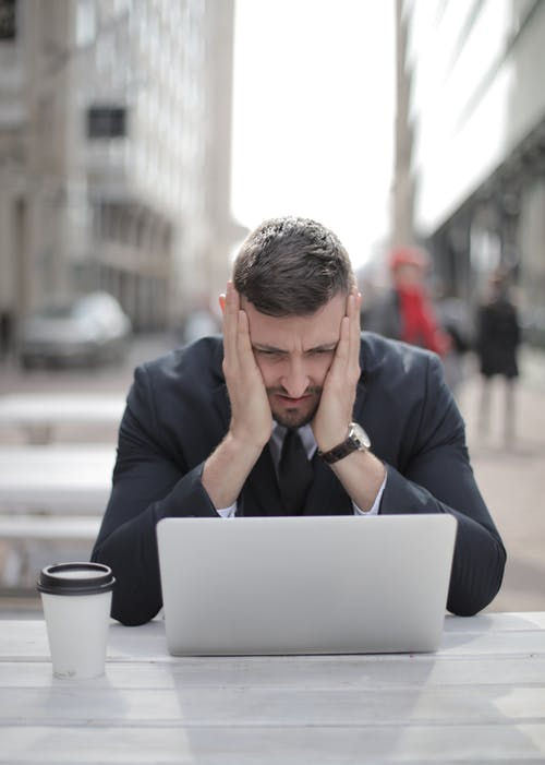 Pensive Man Looking at Computer Laptop