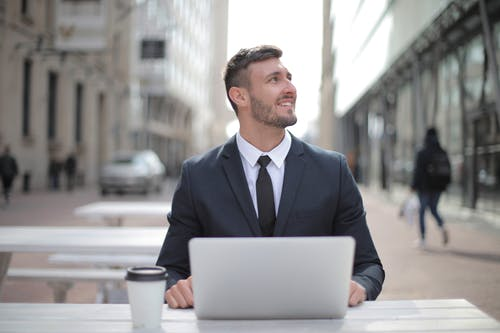 Man in Black Suit Jacket Using Macbook
