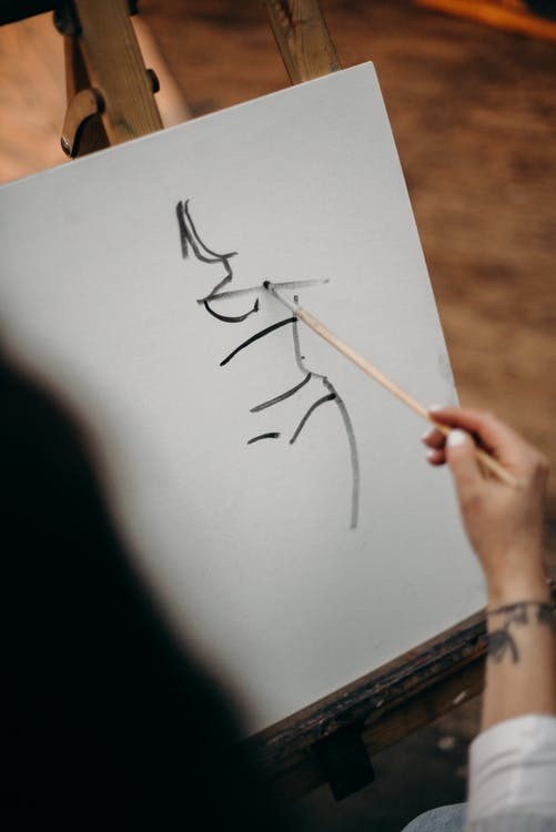 Person Holding Wooden Brush Drawing on White Canvas