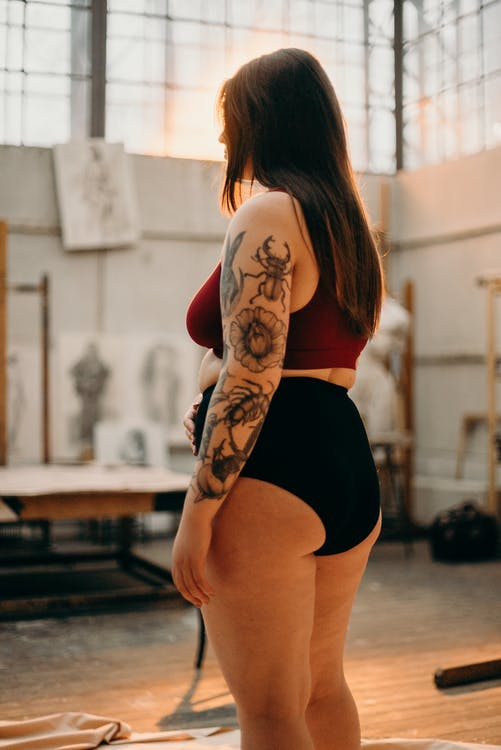 Woman in Black Underwear With Black Floral Tattoo on Her Arm