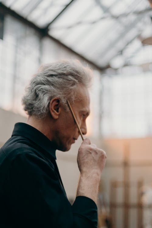 Side View Photo of Elderly Man Holding a Paint Brush