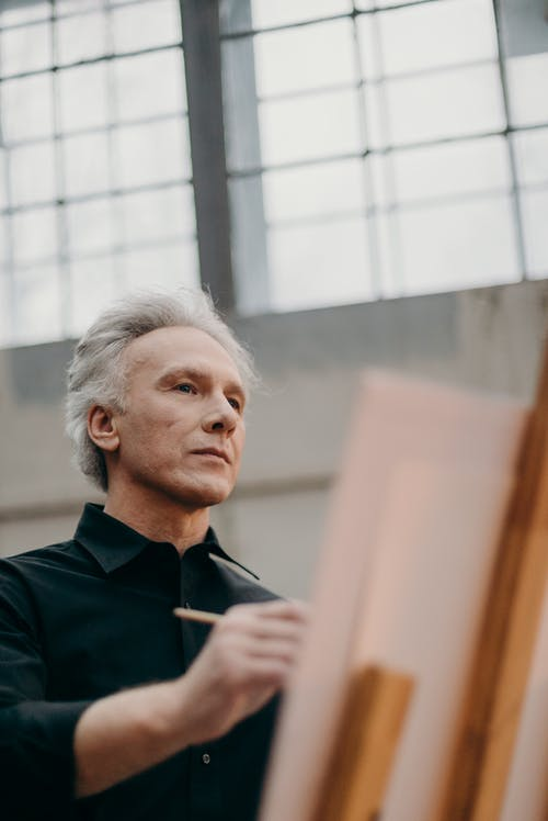 Man in Black Long Sleeves Holding a Paintbrush