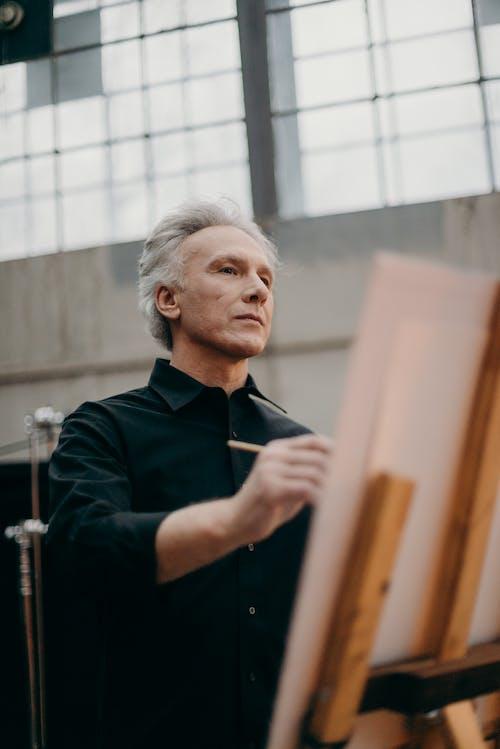 Elderly Man Sketching on White Cardboard