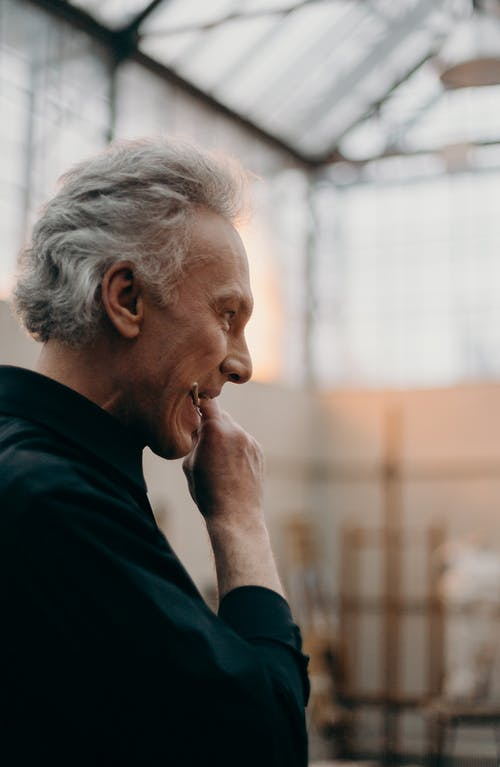 Man in Black Long Sleeve Biting a Paintbrush