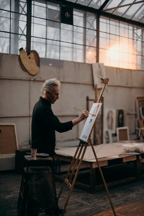 A Serious Man Painting On a White Cardboard