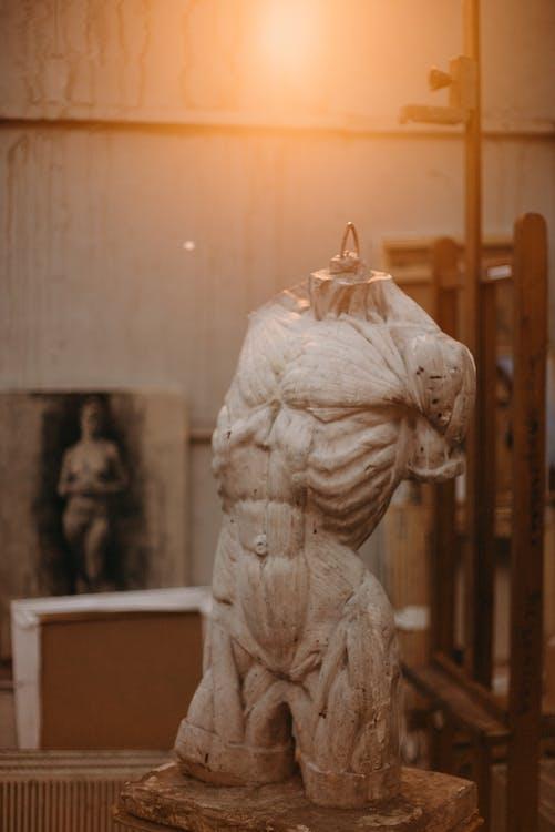 Weiße Konkrete Statue Des Mannes Unter Der Glühbirne