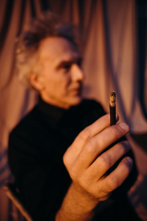 Man in Black Shirt Holding Cigarette Stick