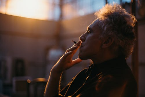 Side View Of A Man In Black Shirt Smoking Cigarette