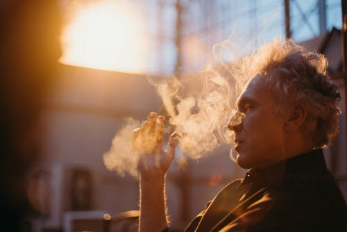 Side View Photo of a Man Smoking Cigarette
