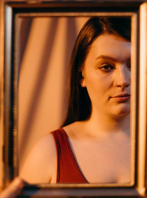 Mujer En Camiseta Roja Sosteniendo Un Espejo