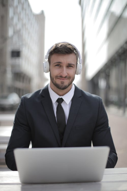 Man in Black Suit Jacket Wearing White Headphones