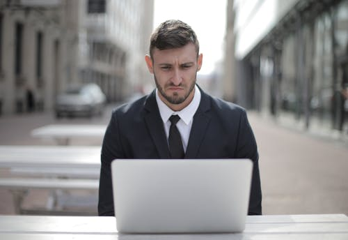 Man in Black Suit Jacket Using Computer Laptop
