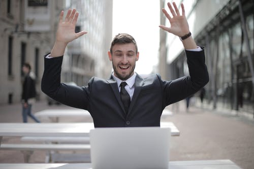 Man in Black Suit Raising Both Hands