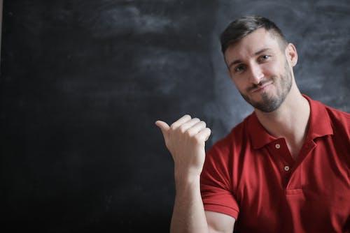 Man in Red Polo Shirt Sitting Beside Chalkboard