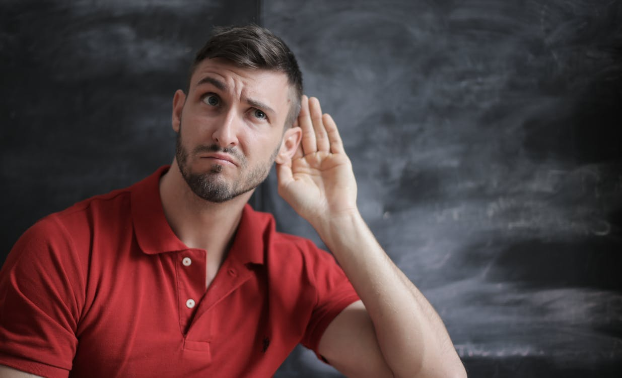Man in Red Polo Shirt Sitting Near Chalkboard