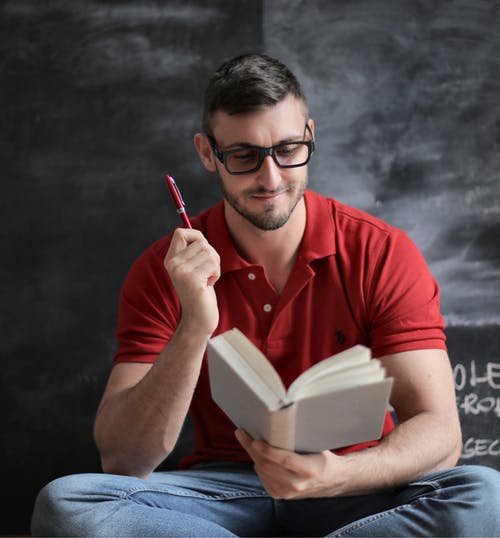 Man in Red Polo Shirt and Blue Denim Jeans Holding Red Pen and Book