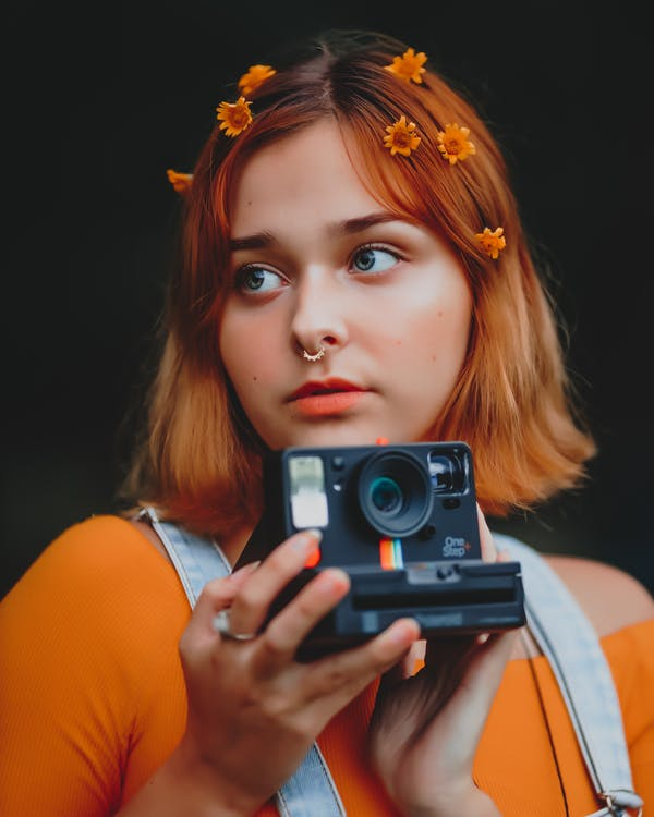 Woman in Orange Tank Top Holding Gray and Black Camera