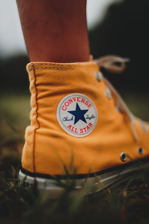Person in Orange and Black Converse All Star High Top Sneakers