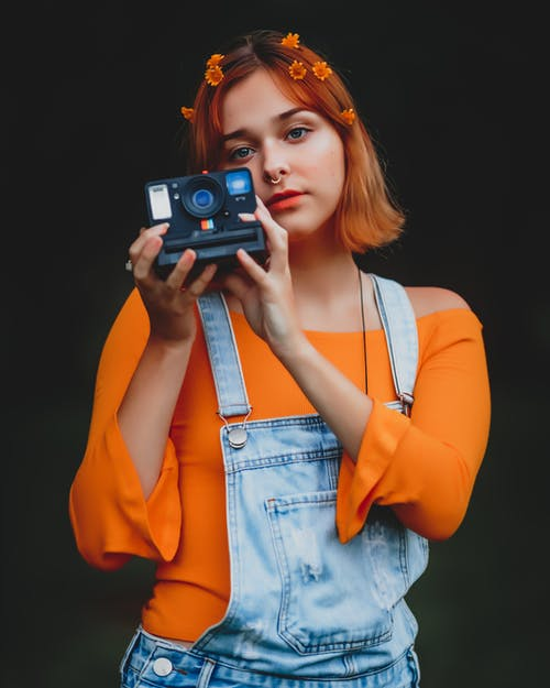 Woman in Orange Blazer Holding Camera