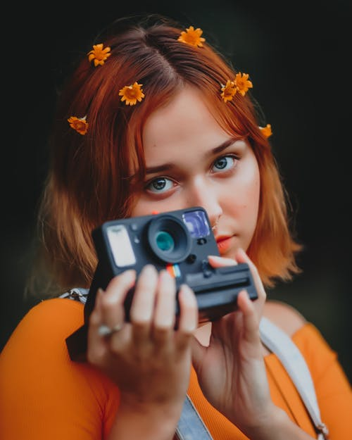 Woman in Orange Shirt Holding Camera