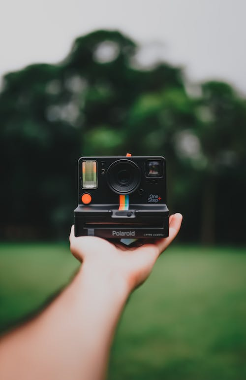 Black Polaroid Camera on Person's Hand