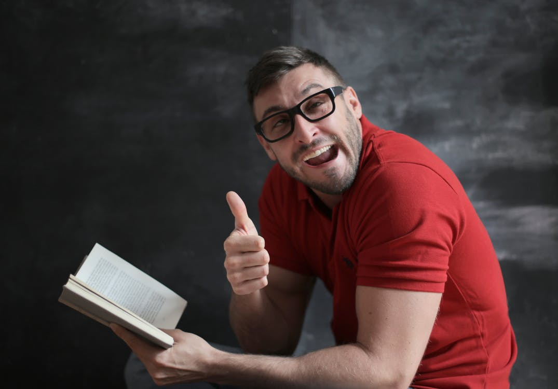 Man in Red Crew Neck T-shirt Wearing Black Framed Eyeglasses Holding White Book