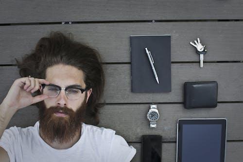 Flat Lay Gadgets Beside Bearded Man