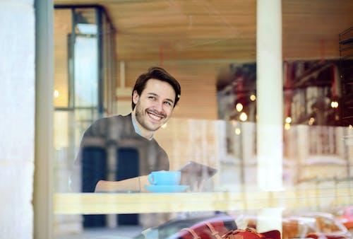 Woman in Blue Long Sleeve  Shirt Sitting Beside Glass Window