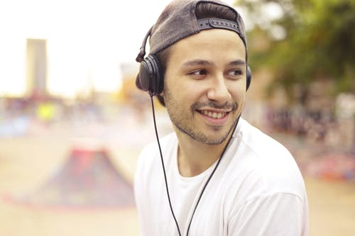 Man in White Crew Neck Shirt Wearing Black Headphones