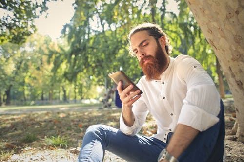 Man in White Dress Shirt and Blue Denim Jeans Sitting on Ground