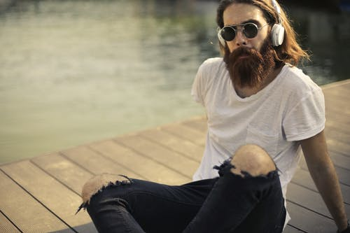 Man in White Crew Neck T-shirt and Blue Denim Jeans Sitting on Brown Wooden Planks